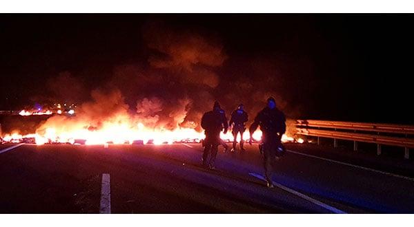 Agentes de policía junto a barricadas en llamas que intentaron bloquear la autopista AP7 durante una huelga general cerca de Girona.