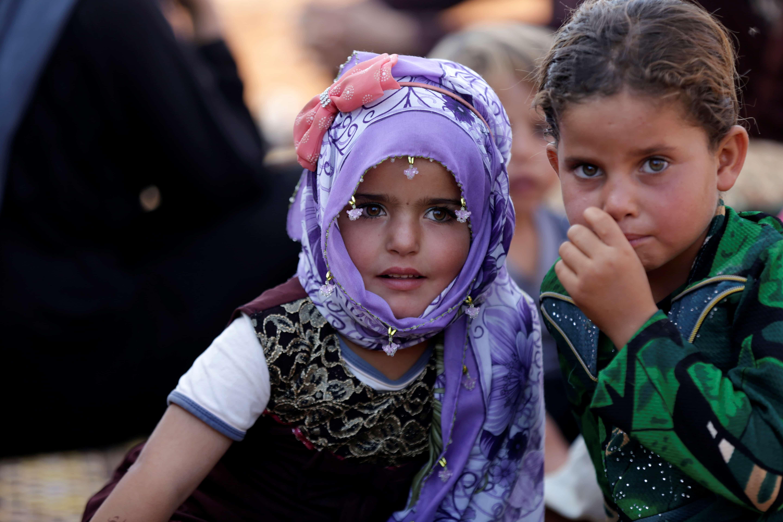 Niños sirios desplazados al arribar a un campamento de refugiados en la aldea de Atimah, provincia de Idlib, Siria.