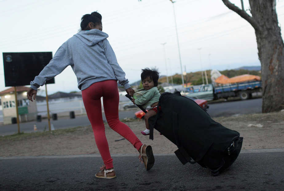 A woman pulls a suitcase with a child sitting on top, after crossing the border from Venezuela to Brazil in Pacaraima, Roraima state, Brazil, February 22, 2019. REUTERS/Ricardo Moraes