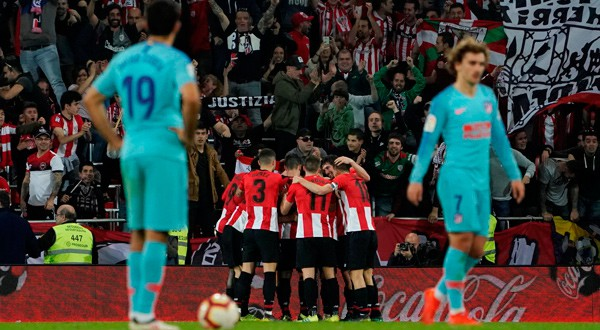Jugadores del Bilbao celebran ante la decepción del Atlético.