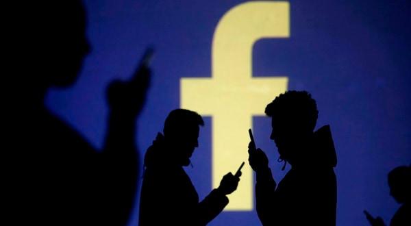 Siluetas de personas entre un logo de Facebook.
