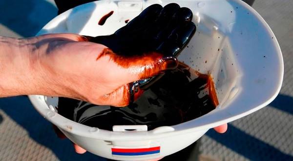 Empleados exhiben muestra de crudo de pozo en planta de procesamiento de yacimiento Priobskoye de Rosneft, en las afueras de Nefteyugansk.