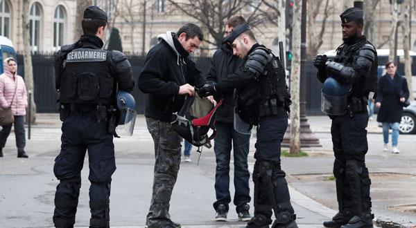 Gendarmes franceses registran a viandantes en la avenida de los Campos Elíseos antes de la nueva protesta de los en París, Francia, el 23 de marzo de 2019