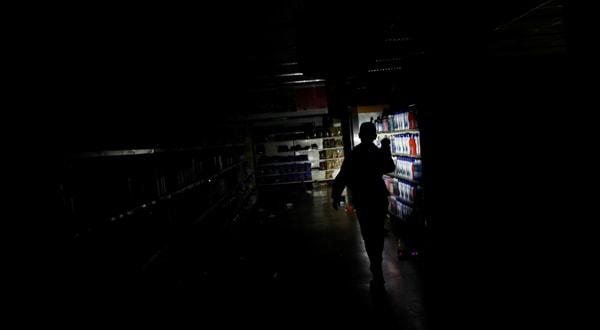 Empleado revisa daños después de saqueos en un supemercado en Caracas