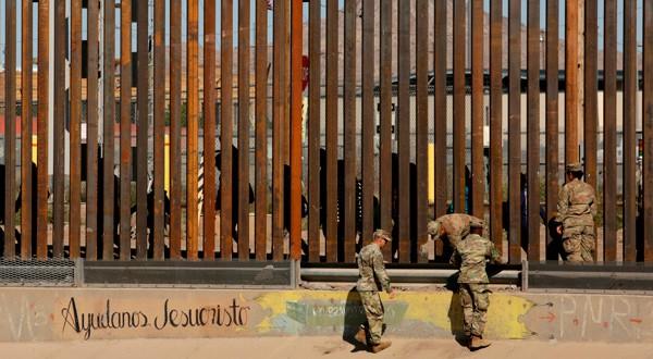 Soldados estadounidenses caminan junto a la cerca fronteriza entre México y Estados Unidos en El Paso, Texas.