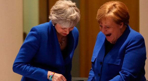 La primera ministra británica Theresa May y la canciller alemana Angela Merkel (derecha) miran una tablet durante una cumbre de líderes europeos en Bruselas, el 10 de abril de 2019.