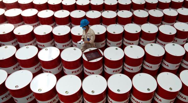 Un trabajador etiqueta barriles de lubricante de petróleo.