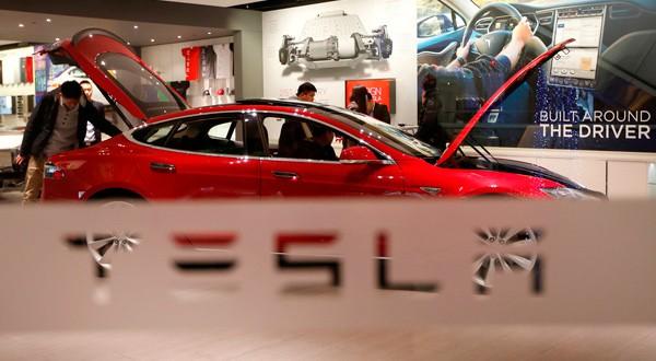 Un hombre mira un auto de Tesla en un lugar de exhibición en Pekín, China.