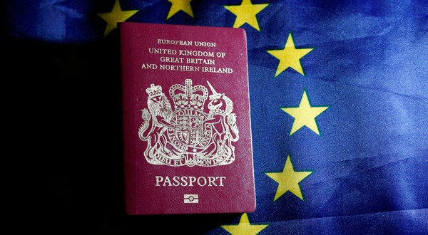 Un pasaporte británico frente a una bandera de la Unión Europea.