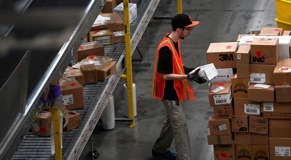 Empleado moviendo paquetes en un centro de almacenamiento de Amazon en Baltimore, Maryland.