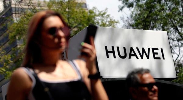 Transeúntes caminando frente a un logo de Huawei en Ciudad de México.