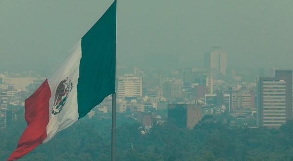 Una vista general muestra la bandera de México enfrente de unos edificios cubiertos por la contaminación atmosférica en Ciudad de México.
