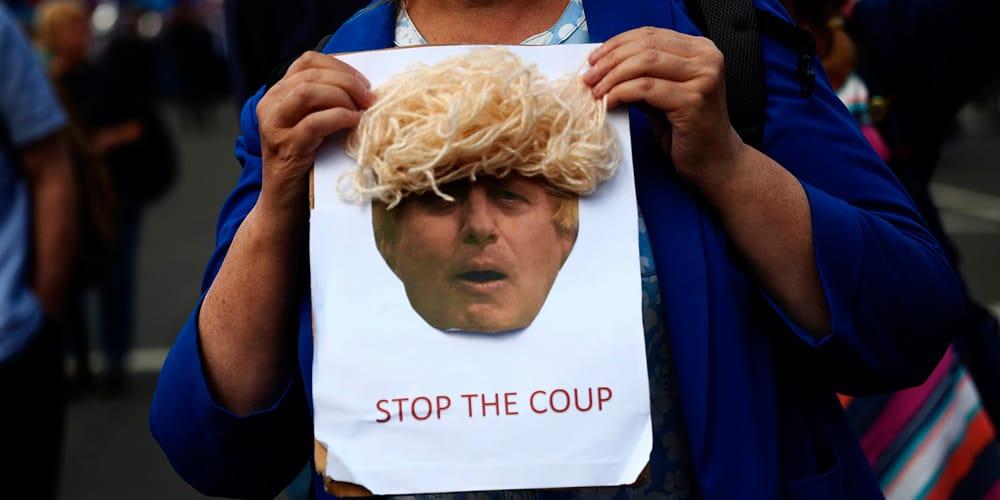 """""""Detengan el golpe"""". Personas protestan durante la sesión a las afueras del Parlamento británico."""