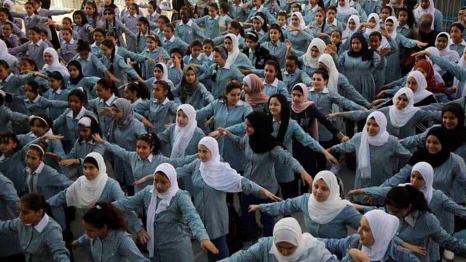 Estudiantes palestinas participan en una actividad matutina en una escuela administrada por las Naciones Unidas en el campo de refugiados de al-Fari'ah en Cisjordania ocupada por Israel. 25 agosto 2019.