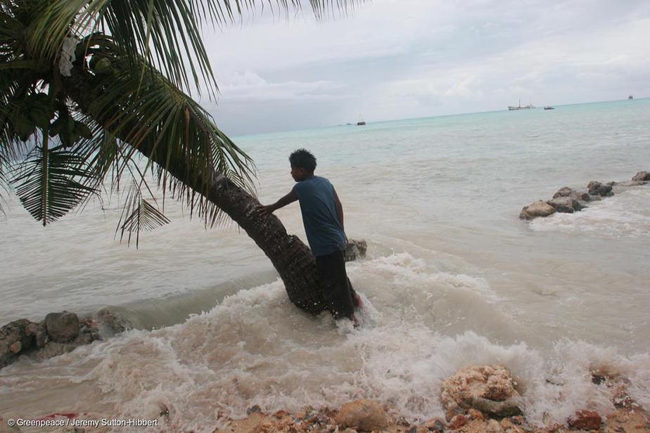 Residente local se apoya contra una palmera mientras las altas olas causadas por las 'Mareas del Rey' entran en la propiedad de su familia, Betio Villge, Isla Tarawa, Kiribati, Océano Pacífico.
