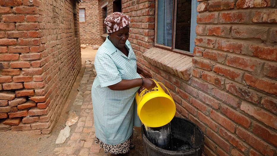 Una mujer vierte el agua recolectada de un camión cisterna municipal en un contenedor de almacenamiento en un municipio en Graaff-Reinet, Sudáfrica. Foto tomada el 17 de noviembre de 2019 por Mike Hutchings