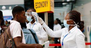 Una trabajadora de la salud chequea la temperatura de un viajero en el aeropuerto internacional de Kotoka en Accra, Ghana, como parte de las medidas para evitar la propagación del coronavirus