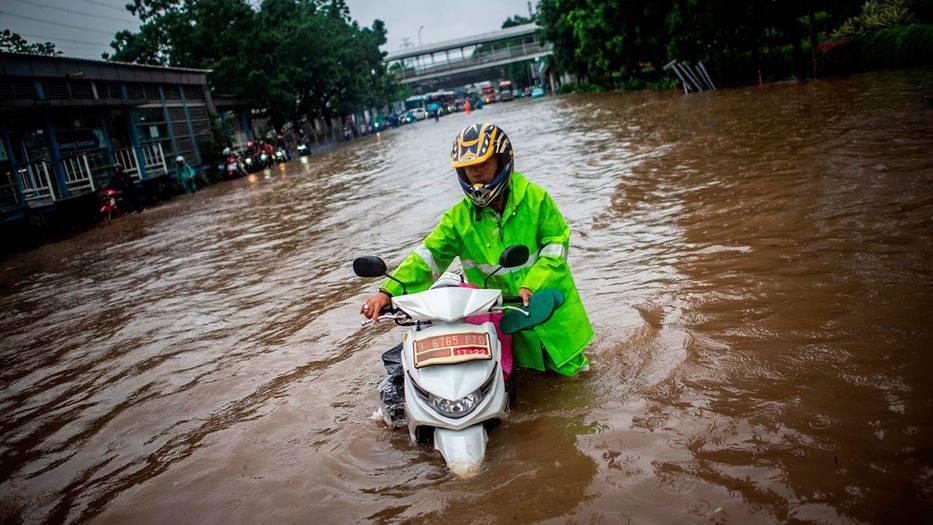 Un hombre camina con su scooter en una carretera inundada, tras fuertes lluvias en Yakarta (Indonesia), el 1 de enero de 2020. Antara Foto / Aprillio Akbar