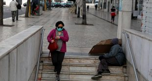 En la esquina de Rossio, en Lisboa, una mujer con mascarilla para evitar la propagación del COVID-19 entra a la estación del metro, el 19 de marzo