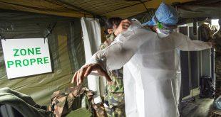 Un efectivo militar ayuda a un trabajador sanitaria a asegurarse su equipo de protección