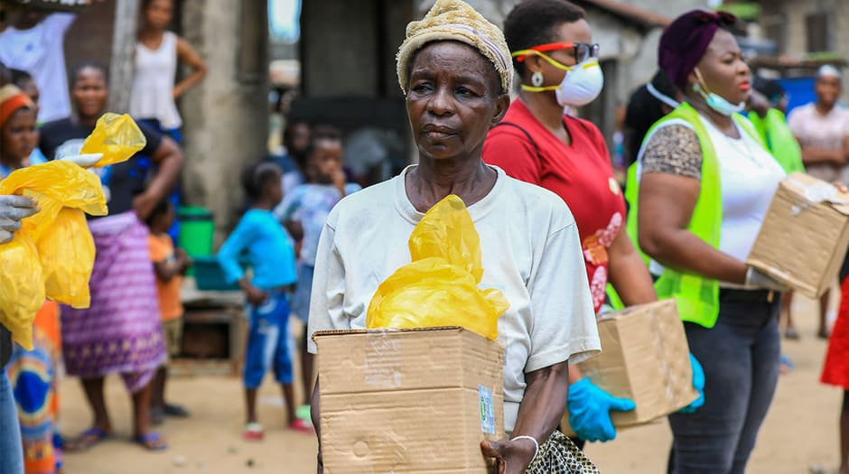 Una mujer mayor recibe en Lagos (Nigeria) comida por parte de organizaciones voluntarias