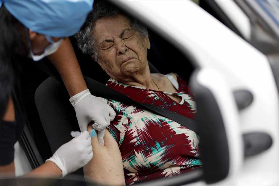 A health worker vaccinates a woman against the flu, as advised by health officials to facilitate diagnosis for coronavirus, amid the coronavirus disease (COVID-19) outbreak, in Brasilia, Brazil March 23, 2020 REUTERS/Ueslei Marcelino     TPX IMAGES OF THE DAY