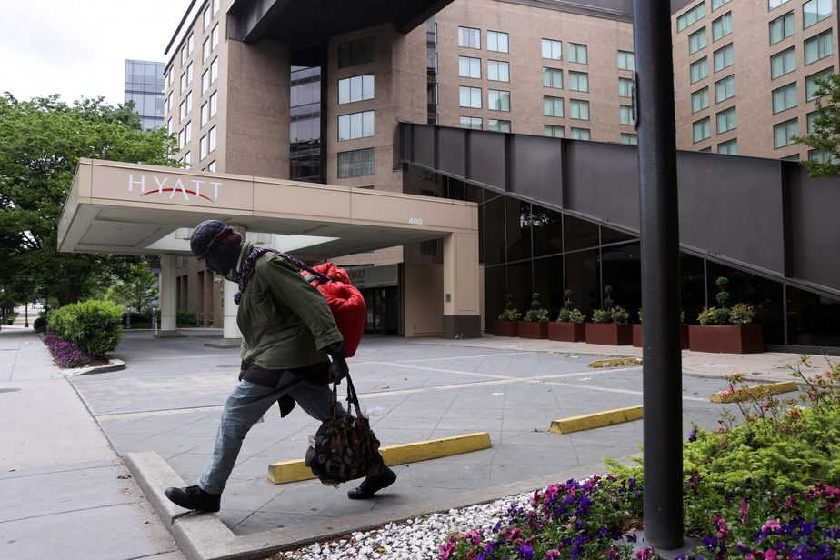 A member of the homeless community walks past a Hyatt hotel that is completely closed to guests during the coronavirus disease (COVID-19) outbreak, in Washington, U.S. May 8, 2020. New unemployment data shows the U.S. economy lost a staggering 20.5 million jobs in April. REUTERS/Jonathan Ernst