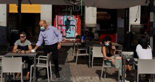 Un camarero que usa una máscara facial protectora sirve una bebida para un cliente en una sección de un restaurante al aire libre que reabrió por primera vez en más de 2 meses en medio del brote de la enfermedad por coronavirus (COVID-19), en la Plaza Mayor de Madrid, España, 25 de mayo de 2020. REUTERS / Juan Medina