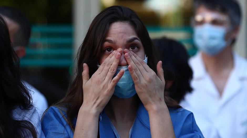 Un miembro del personal médico del hospital Fundación Jiménez Díaz reacciona mientras las personas aplauden desde sus balcones en apoyo de los trabajadores de la salud, ya que se espera que sea el último día de aplausos, en medio del brote de la enfermedad por coronavirus (COVID-19), en Madrid, España, 17 de mayo de 2020. REUTERS / Sergio Perez