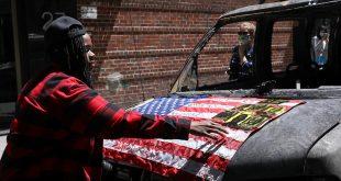 Una mujer pone una bandera en una camioneta de NYPD quemada durante los disturbios en todo el país tras la muerte en custodia policial de George Floyd. Manhattan, Nueva York, EE. UU., 31 de mayo de 2020. REUTERS / Caitlin Ochs