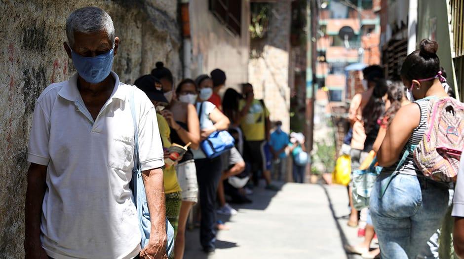 La gente hace una fila para recibir alimentos de una organización benéfica, en el barrio de Carapita, durante la cuarentena nacional debido al brote de la enfermedad por coronavirus (COVID-19), en Caracas, Venezuela, 30 de abril de 2020. Fotografía tomada el 30 de abril de 2020. REUTERS / Manaure Quintero