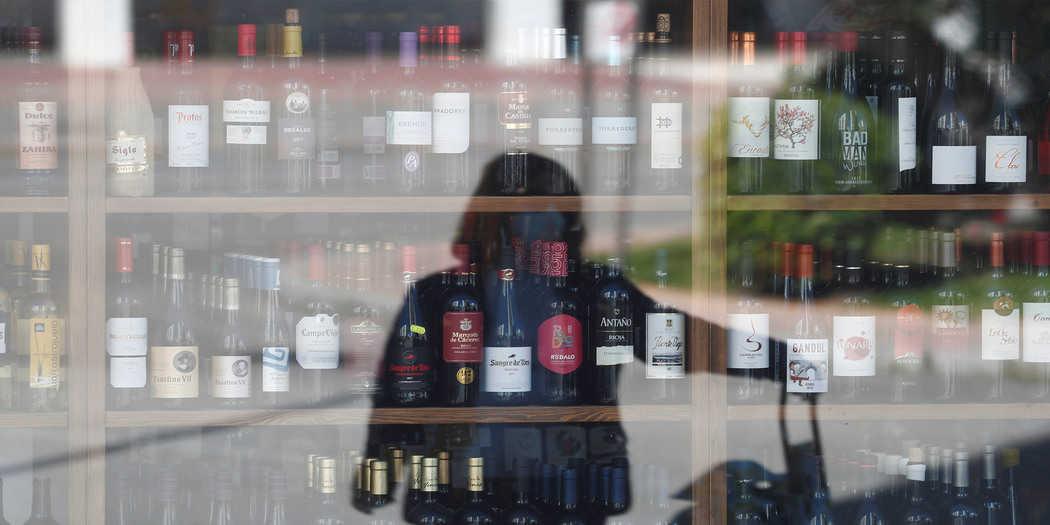 Una mujer se refleja en el escaparate de una tienda mientras espera entrar, durante el brote de la enfermedad por coronavirus (COVID-19), en Ronda, sur de España, el 3 de abril de 2020. REUTERS / Jon Nazca