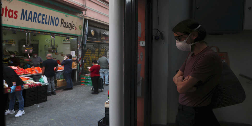 Un hombre que lleva una máscara facial protectora mantiene la distancia social mientras espera comprar en un puesto de frutas, en medio del brote de la enfermedad del coronavirus (COVID-19), en Madrid, España, 5 de mayo de 2020. REUTERS / Susana Vera