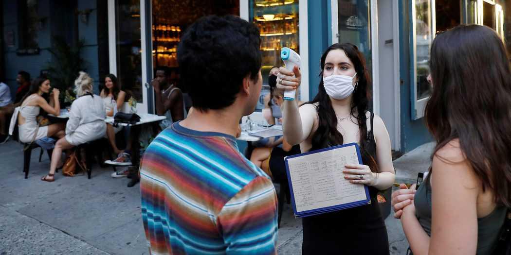 Una camarera toma la temperatura de los clientes cuando llegan a comer, como parte de la reapertura de la fase 2 durante el brote de la enfermedad por coronavirus (COVID-19) en Manhattan, EE. UU. 27 de junio de 2020. REUTERS / Andrew Kelly