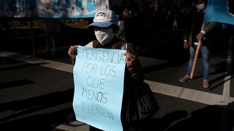 """Un manifestante con una máscara facial sostiene un cartel que dice """"emergencia para los que menos tienen"""", durante una protesta para exigir recursos para los vulnerables, en medio de la enfermedad por coronavirus (COVID-19), en Buenos Aires, Argentina, el 11 de junio de 2020. REUTERS / Agustin Marcarian / Foto de archivo"""
