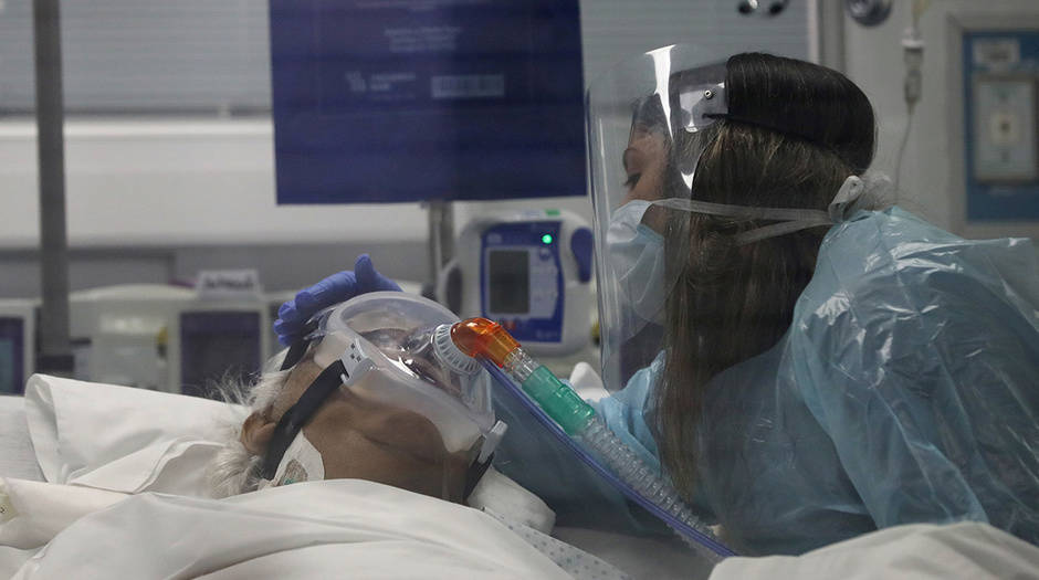 Un pariente toca a Jaime, de 76 años, infectado con la enfermedad por coronavirus durante un último adiós dentro de una Unidad de Cuidados Intensivos del hospital clínico de la Universidad de Chile en Santiago, Chile, 18 de junio de 2020. Foto. REUTERS / Iván Alvarado