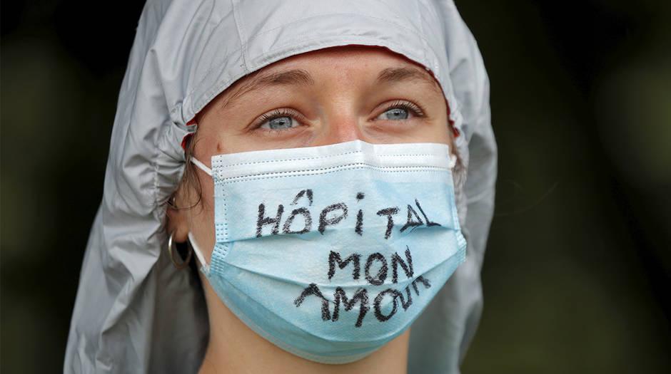 """Un trabajador de la salud francés asiste a una protesta en París como parte de un día nacional de acciones para instar al gobierno a mejorar los salarios e invertir en hospitales públicos. Francia el 16 de junio de 2020. El lema dice """"Hospital my love"""". REUTERS / Charles Platiau"""