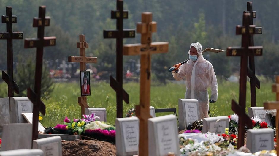 Un sepulturero con equipo de protección personal camina después de enterrar a una persona, que presumiblemente murió de la enfermedad por coronavirus (COVID-19) en un cementerio en las afueras de San Petersburgo, Rusia, 10 de junio de 2020. REUTERS / Anton Vaganov