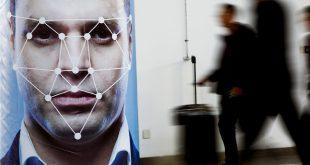 La gente pasa junto a un póster que simula el software de reconocimiento facial en la exposición Security China 2018 sobre seguridad pública en Beijing, China, 24 de octubre de 2018. REUTERS / Thomas Peter