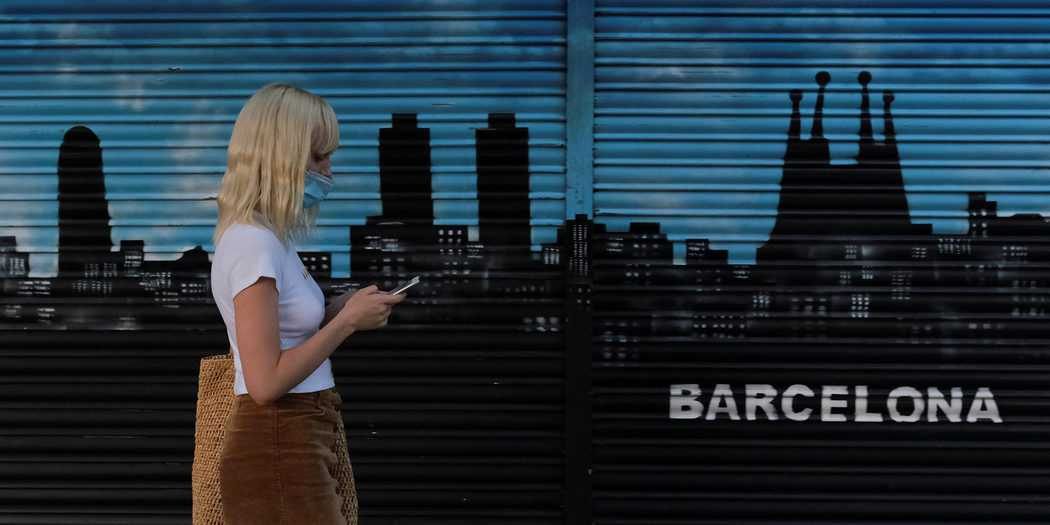 Una mujer con una máscara facial mira su teléfono móvil después de que las autoridades regionales de Cataluña y el ayuntamiento anunciaran restricciones para contener la propagación de la enfermedad por coronavirus (COVID-19) en Barcelona, España, 21 de julio de 2020. REUTERS / Nacho Doce