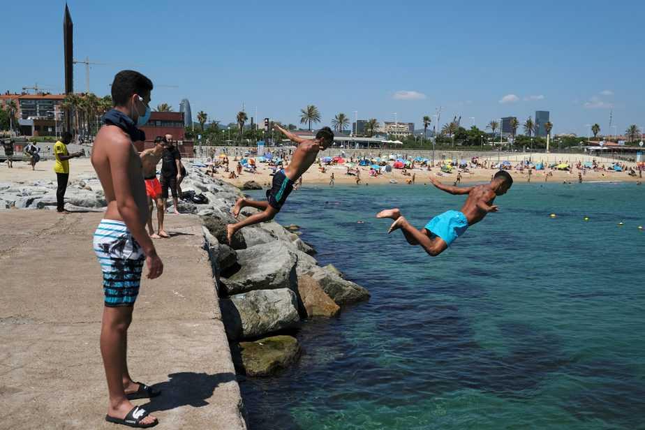Hombres se lanzan al agua mientras que disfrutan del sol en la playa después de que se anunciaron limitaciones para contener la propagación de la enfermedad por el nuevo coronavirus COVID-19 en Barcelona, España. 19 de julio de 2020. REUTERS/Nacho Doce