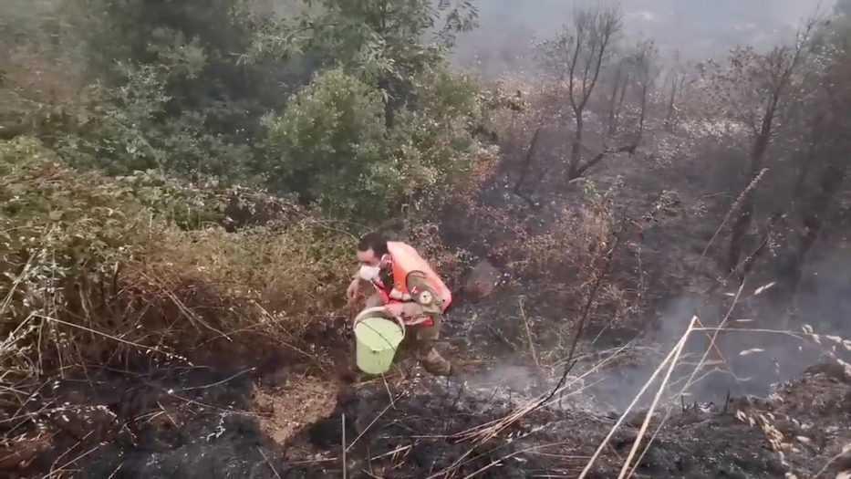 Un bombero voluntario camina para llenar un balde de agua a fin de controlar el incendio forestal de Monte Fundeiro el 26 de julio de 2020. Imagen fija que se tomó de un video de las redes sociales. Aprosoc por vía REUTERS.
