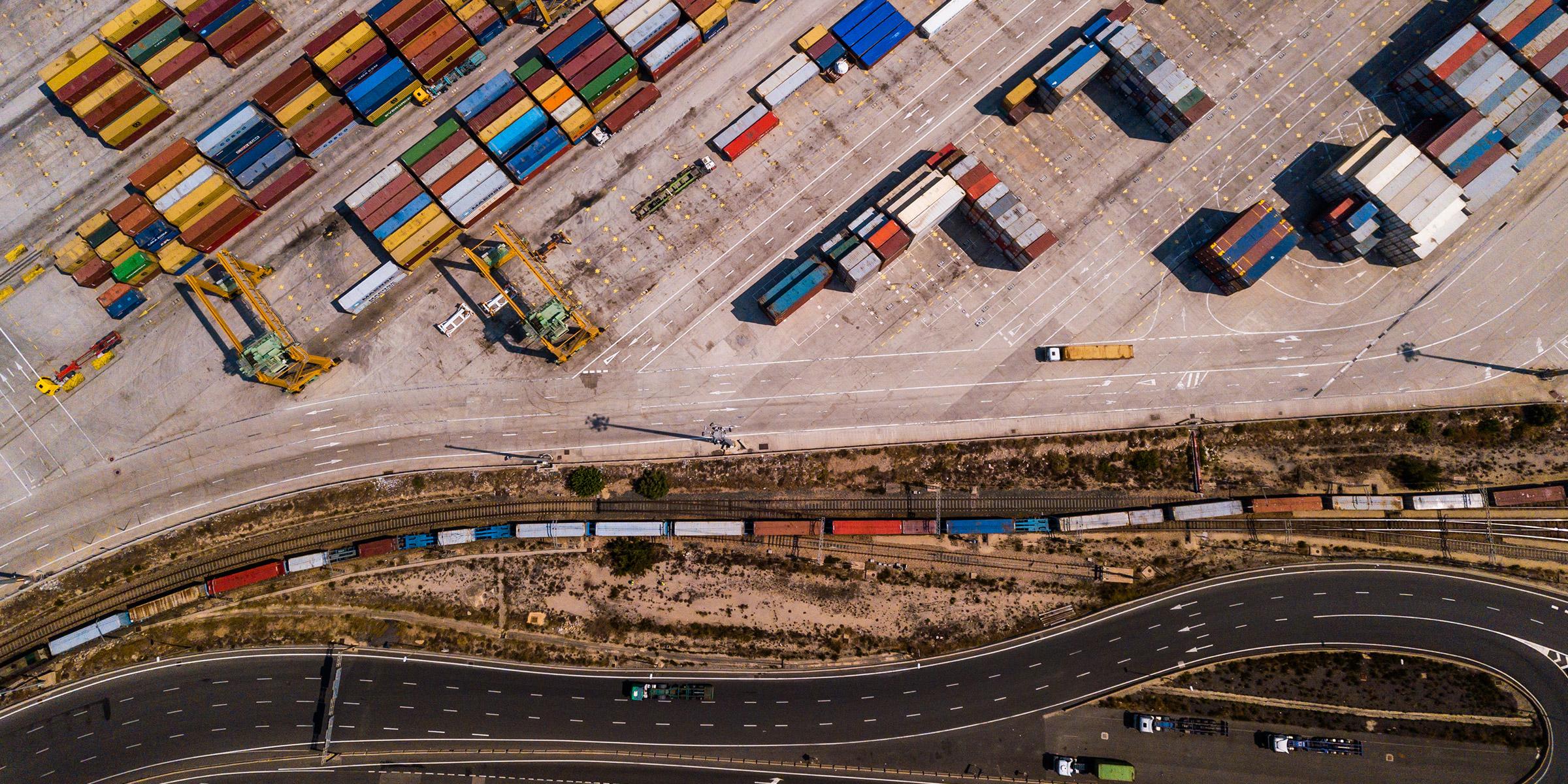 Área de carga industrial con buque portacontenedores, vista aérea del muelle de transporte. Valencia, España.