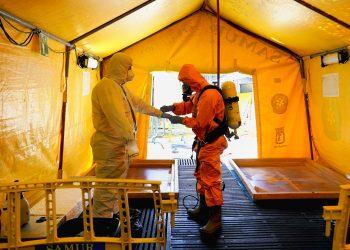 Un miembro del Servicio de Ambulancias ajusta el equipo de protección de su colega, durante la pandemia de la enfermedad del coronavirus (COVID-19), en su sede en Madrid, España. REUTERS / Juan Medina