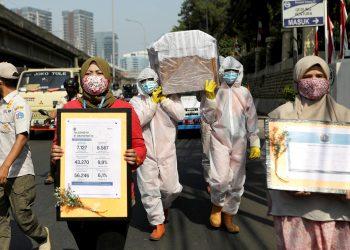 Los trabajadores del gobierno que visten trajes protectores llevan una maqueta de un ataúd de una víctima de la enfermedad por coronavirus (COVID-19) mientras que otros llevan carteles que muestran información sobre la cantidad de casos de COVID-19 para advertir a las personas sobre los peligros de la enfermedad. mientras continúa el brote en Yakarta, Indonesia, el 28 de agosto de 2020. REUTERS / Willy Kurniawan