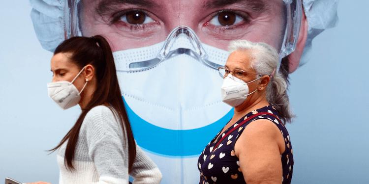 Personas, con máscaras protectoras, pasan por un anuncio de clínica dental en el barrio de Vallecas en Madrid