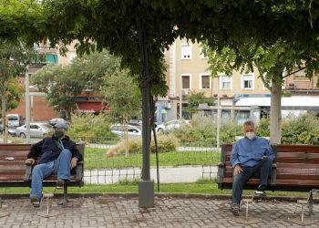 Personas con mascarillas protectoras descansan en los bancos en el barrio de Carabanchel, en Madrid, España | REUTERS / Javier Barbancho