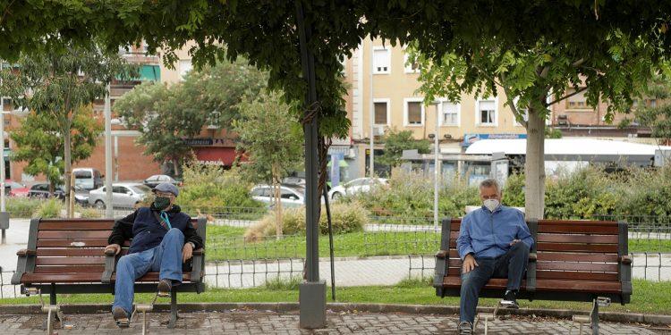 Personas con mascarillas protectoras descansan en los bancos en el barrio de Carabanchel, en Madrid, España   REUTERS / Javier Barbancho