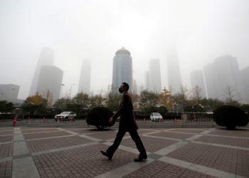 """Un hombre que tiene puesta una mascarilla camina por el distrito comercial del centro de Pekín durante un día contaminado y después de que se emitió una alerta amarilla por """"smog"""". Pekín, China, 14 de noviembre de 2018. REUTERS / Jason Lee. Foto de archivo"""