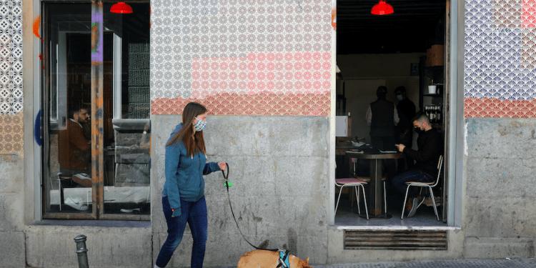 Mujer con un perro pasa junto a la gente dentro de un bar en el centro de Madrid.